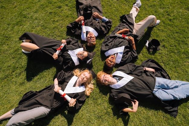 Glückliche absolventen, die ihre diplome zusammen auf dem rasen vor der universität liegend halten