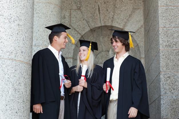Glückliche absolventen, die zusammen sprechen