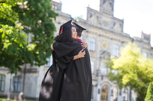 Glückliche absolventen. freunde umarmen sich nach dem abschluss und fühlen sich glücklich