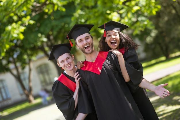 Glückliche absolventen. gruppe von absolventen, die im park stehen und sich großartig fühlen
