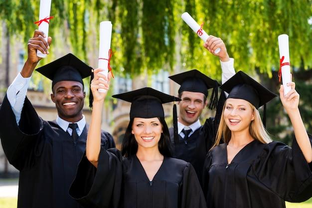 Glückliche absolventen. vier hochschulabsolventen zeigen ihre diplome und lächeln, während sie nahe beieinander stehen und
