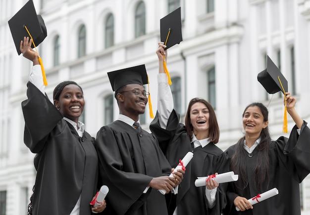 Glückliche absolventen werfen mützen auf