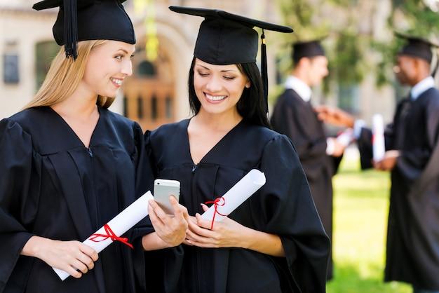 Glückliche absolventen. zwei glückliche frauen in abschlusskleidern, die zusammen auf das handy schauen und lächeln, während zwei männer im hintergrund stehen