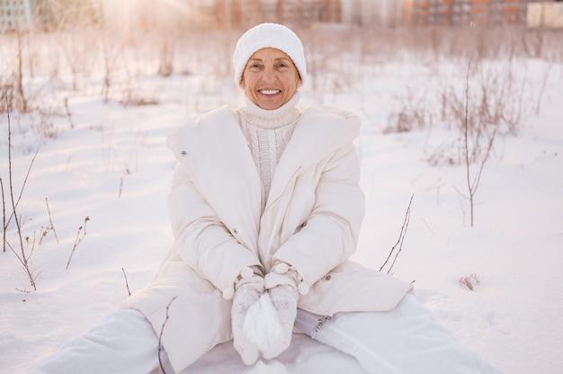 Glückliche ältere ältere reife frau in der weißen warmen oberbekleidung, die mit schnee im sonnigen winter draußen spielt.