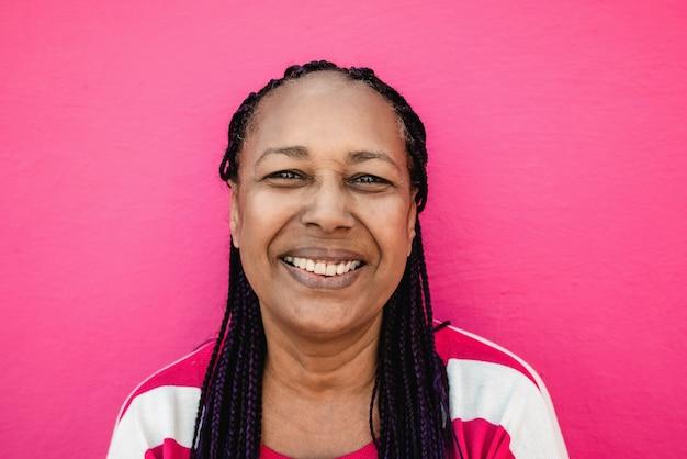 Glückliche ältere afrikanische frau, die vor der kamera im freien lächelt - fokus auf gesicht