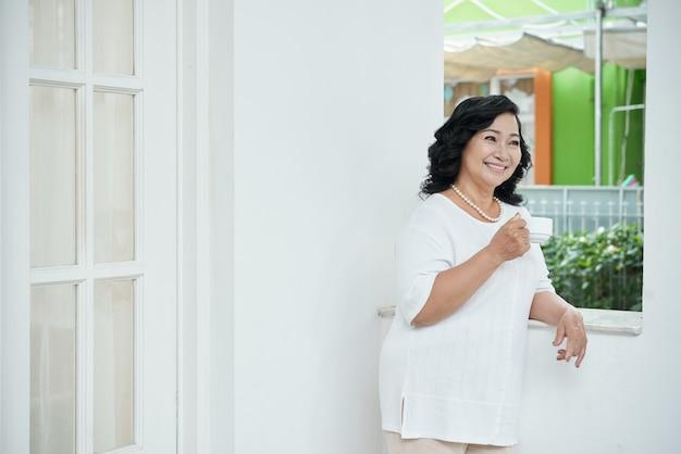 Glückliche ältere asiatin, die sich zu hause auf balkon lehnt und tasse tee hält