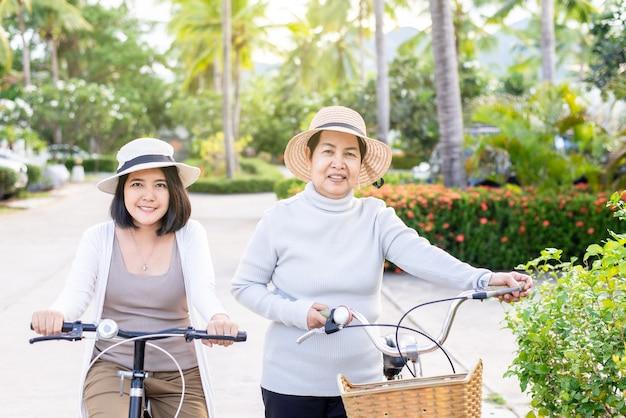 Glückliche ältere asiatische frau, die fahrräder mit tochter am öffentlichen park,