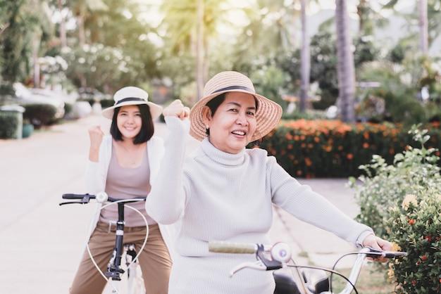 Glückliche ältere asiatische frau, die fahrräder mit tochter am park, fahrrad fährt