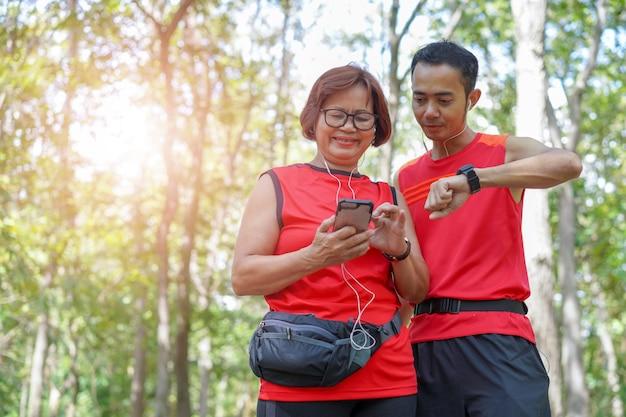 Glückliche ältere asiatische frau mit dem mann oder persönlichem trainer, die zeit von der intelligenten uhr überprüfen