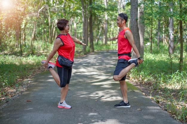 Glückliche ältere asiatische frau mit mann oder persönlichem trainer dehnen oberschenkelmuskeln am park aus