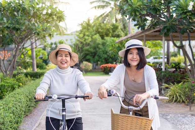 Glückliche ältere asiatische frauen, die fahrrad mit tochter am öffentlichen park radeln,