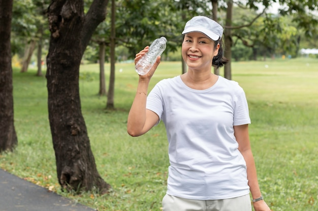 Glückliche ältere asiatische lächelnde frau, die süßwasser im sommer am park trinkt.