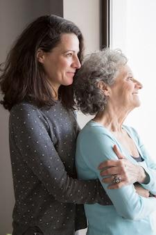 Glückliche ältere dame, die liebe ihrer erwachsenen tochter glaubt