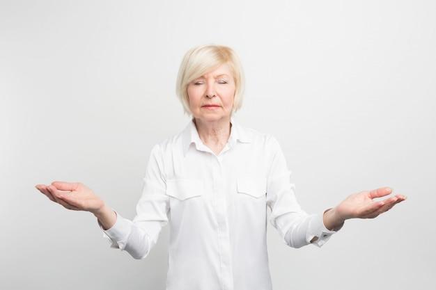 Glückliche ältere dame, die meditiert. sie sucht ruhe und versucht sich selbst zu finden. sie will in ihrem alter glücklich sein.