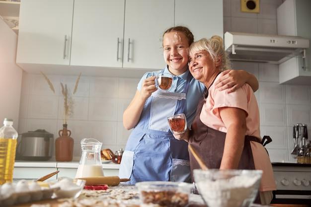 Glückliche ältere dame, die von ihrer enkelin umarmt wird