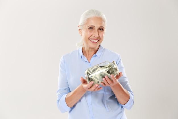 Glückliche ältere dame im blauen hemd, das glasbank mit dollars hält