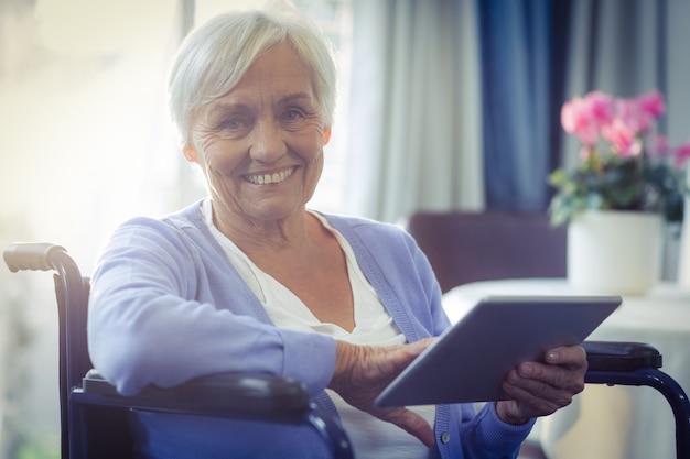 Glückliche ältere frau auf rollstuhl unter verwendung der digitalen tablette