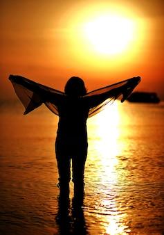 Glückliche ältere frau bei sonnenuntergang am strand