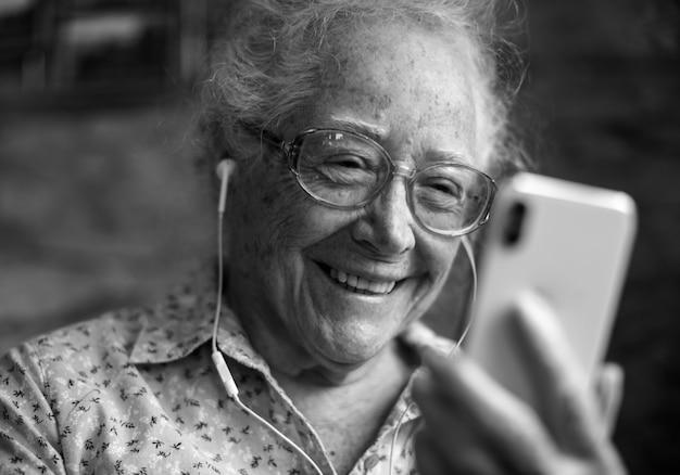Glückliche ältere frau, die am telefon spielt