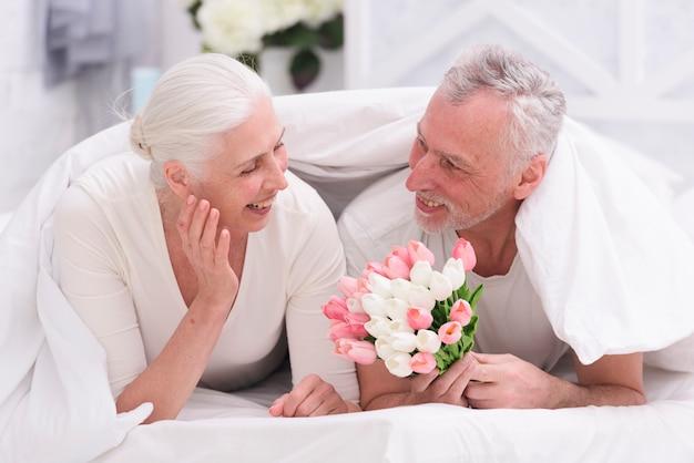 Glückliche ältere frau, die auf dem bett betrachtet die tulpenblumen gehalten von ihrem ehemann liegt