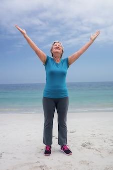 Glückliche ältere frau, die auf dem strand steht