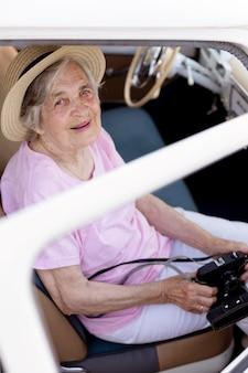 Glückliche ältere frau, die auf reisen eine kamera hält holding