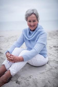 Glückliche ältere frau, die auf strand sitzt