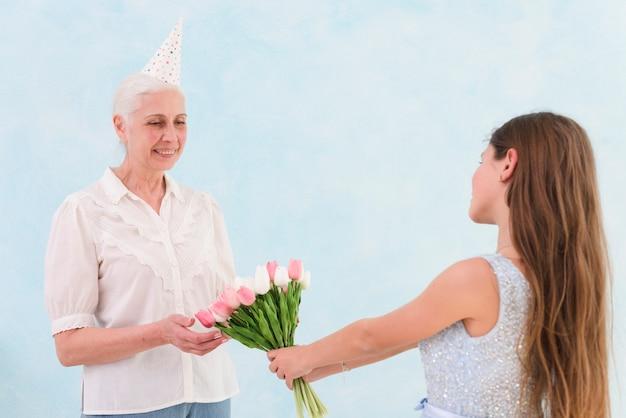 Glückliche ältere frau, die blumenstrauß von tulpenblumen von ihrem enkelkind empfängt