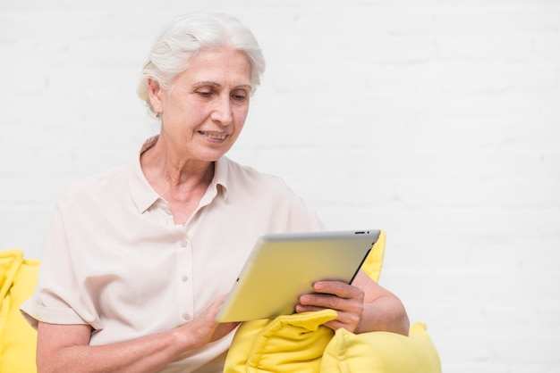 Glückliche ältere frau, die digitale tablette gegen weiße wand betrachtet
