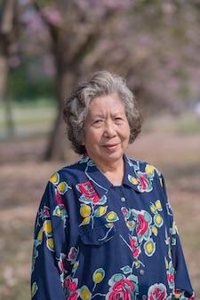 Glückliche ältere frau, die draußen im park steht. ältere asiatische frau, die lächelt und kamera draußen betrachtet