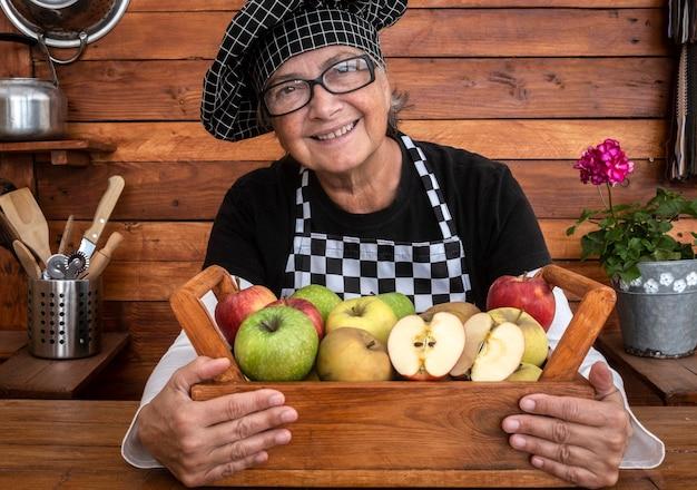 Glückliche ältere frau, die einen korb voller frischer äpfel hält, die bereit sind, verkauft zu werden. konzept für gesunde ernährung. holzkorb und rustikaler hintergrund. bauer stolz auf ihre ernte
