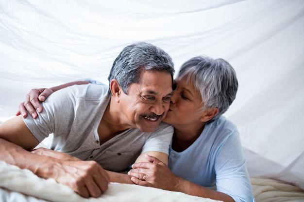Glückliche ältere frau, die einen kuss auf mannbacken gibt