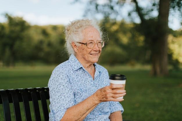 Glückliche ältere frau, die einen mitnehmerkaffee am park trinkt