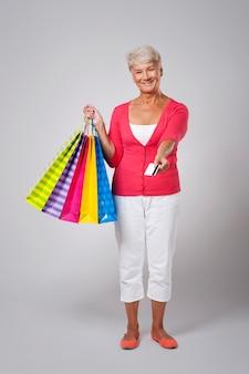 Glückliche ältere frau, die für das einkaufen mit kreditkarte zahlt