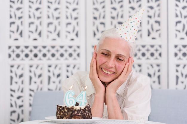Glückliche ältere frau, die geschmackvollen kuchen mit glühenden kerzen auf tabelle betrachtet