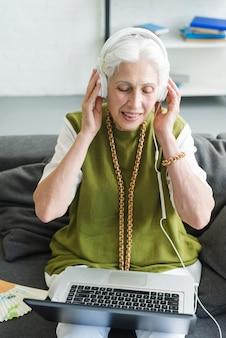 Glückliche ältere frau, die hörende musik des laptops auf kopfhörer betrachtet