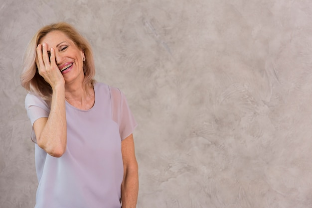 Glückliche ältere frau, die ihr auge mit ihrer hand bedeckt