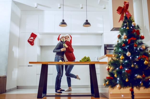 Glückliche ältere frau, die ihre schwangere tochter umarmt. beide haben weihnachtsmützen auf dem kopf und halten bier.