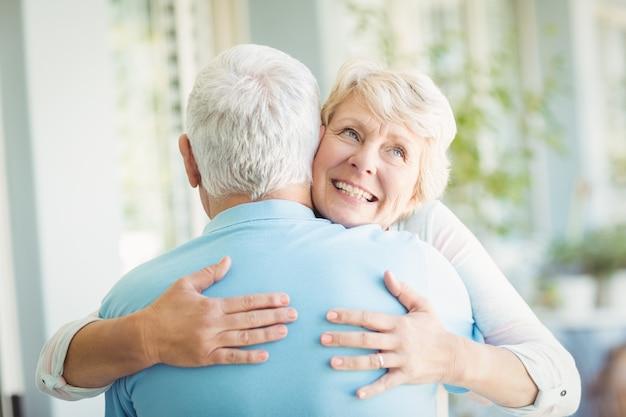 Glückliche ältere frau, die ihren ehemann umarmt