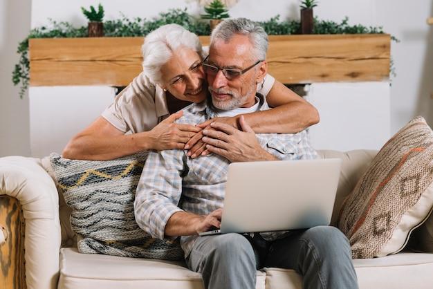 Glückliche ältere frau, die ihren ehemann von hinten sitzt auf sofa mit laptop umfasst