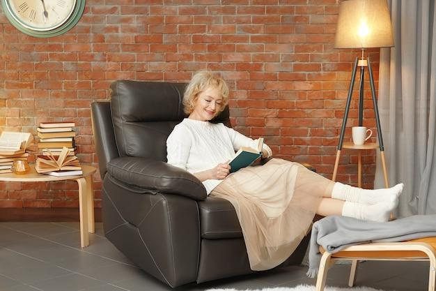 Glückliche ältere frau, die im sessel sitzt und buch liest