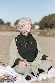 Glückliche ältere frau, die meditiert
