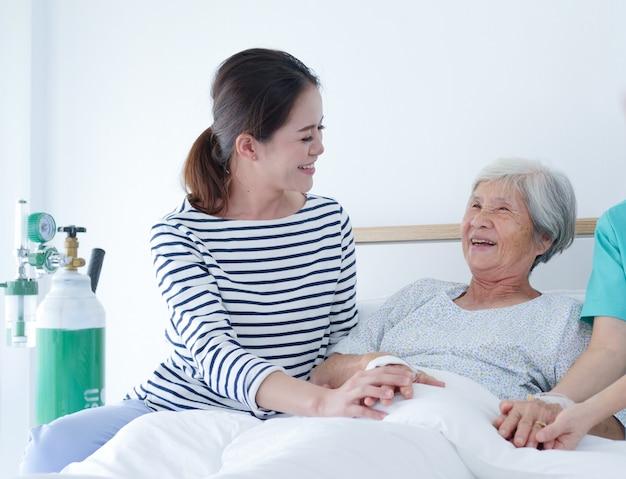 Glückliche ältere frau, die mit älterer krankenschwester und ihrer tochter im krankenhauszimmer spricht.
