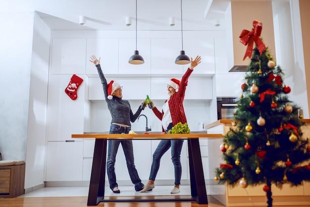 Glückliche ältere frau, die mit bier mit ihrer tochter beim stehen in der küche anstößt. beide haben weihnachtsmützen auf den köpfen.