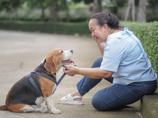 Glückliche ältere frau, die mit einem beagle, entspannungszeitkonzept chattet