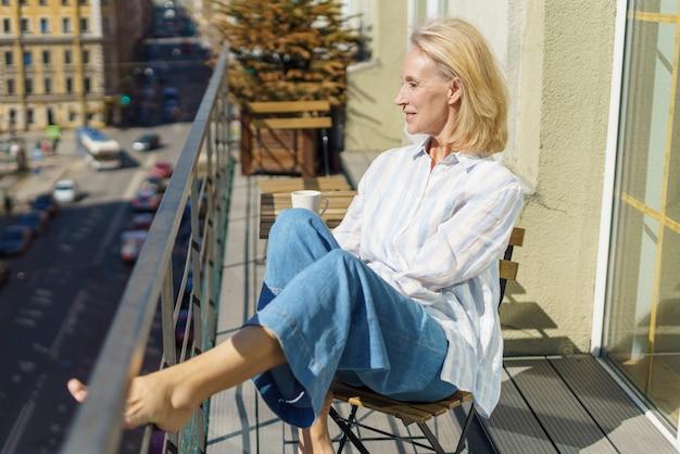 Glückliche ältere frau, die mit einer tasse kaffee auf der terrasse sitzt und einen schönen sonnigen morgen genießt?