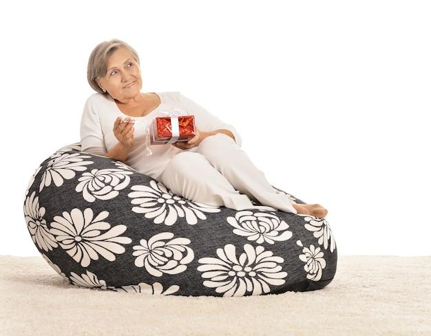 Glückliche ältere frau, die mit geschenk auf schwarzem sessel sitzt