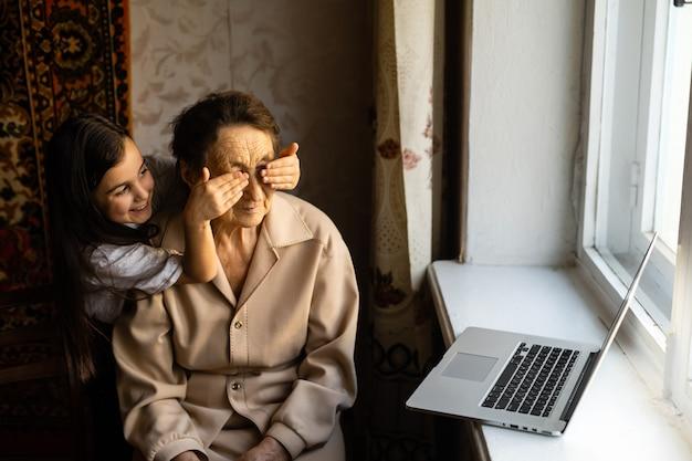 Glückliche ältere frau, die mit ihrer enkelin sitzt und den laptop anschaut, der videoanruf macht. reife dame, die mit der webcam spricht und während der selbstisolation zu hause online-chat macht. familienzeit während corona