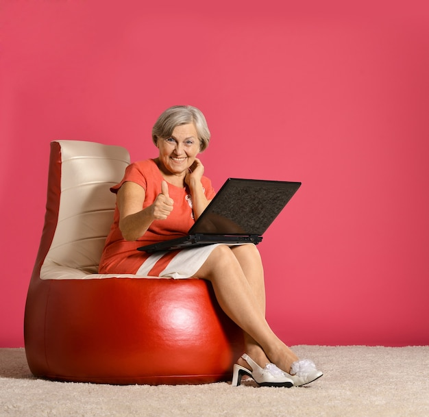 Glückliche ältere frau, die mit laptop auf rotem sessel sitzt