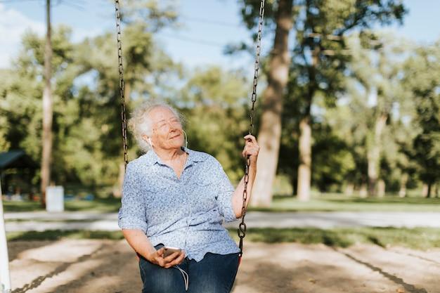 Glückliche ältere frau, die musik auf einem schwingen hört